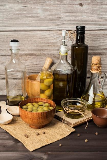 Garrafas de azeite e azeitonas em cima da mesa Foto gratuita
