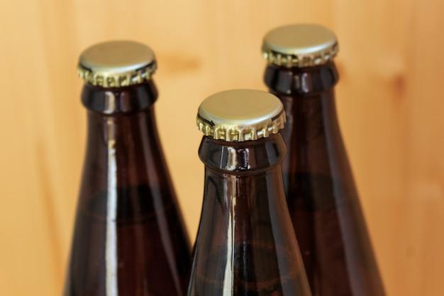 Garrafas de cerveja, bebidas geladas close-up, em fundo de madeira Foto Premium