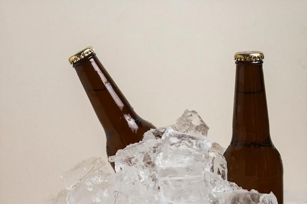 Garrafas de cerveja de alto ângulo em cubos de gelo Foto gratuita