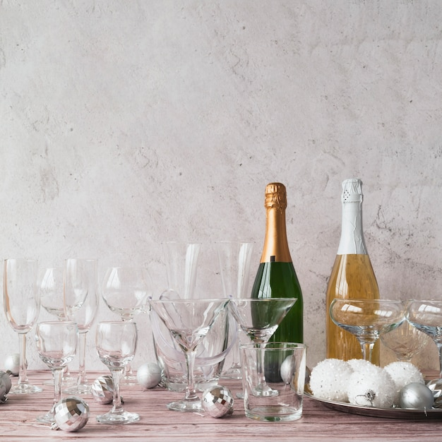 Garrafas de champanhe com copos em cima da mesa Foto gratuita