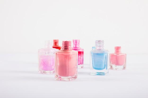 Garrafas de esmalte colorido na superfície branca Foto gratuita