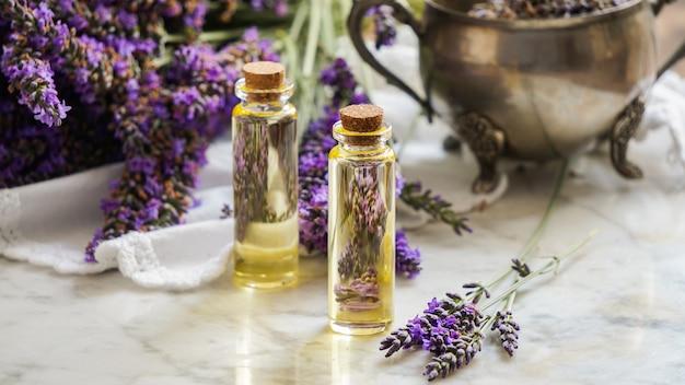Garrafas de óleo de lavanda, erva natural cosméticos com flores de lavanda em fundo de pedra Foto Premium