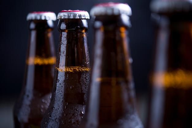 Garrafas de vidro de cerveja com vidro e gelo no fundo escuro Foto gratuita