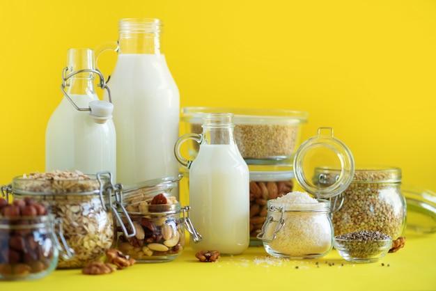Garrafas de vidro do leite da planta do vegetariano e das amêndoas, porcas, coco, leite da semente de cânhamo no fundo amarelo. Foto Premium