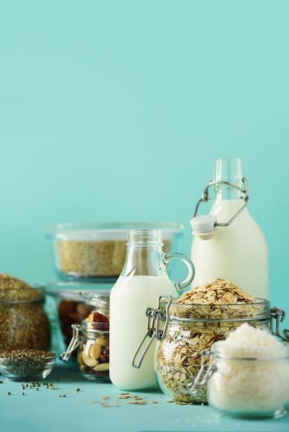 Garrafas de vidro do leite da planta do vegetariano e das amêndoas, porcas, coco, leite da semente de cânhamo no fundo azul. Foto Premium