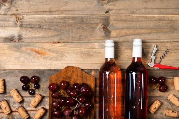 Garrafas de vinho de vista superior com fundo de madeira Foto gratuita