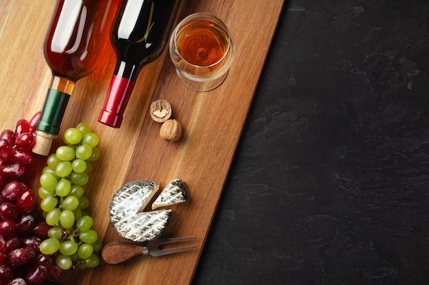 Garrafas de vinho vermelhas e brancas com cacho de uvas, cabeça de queijo, nozes e um copo de vinho na placa de madeira e fundo preto com copyspace Foto Premium