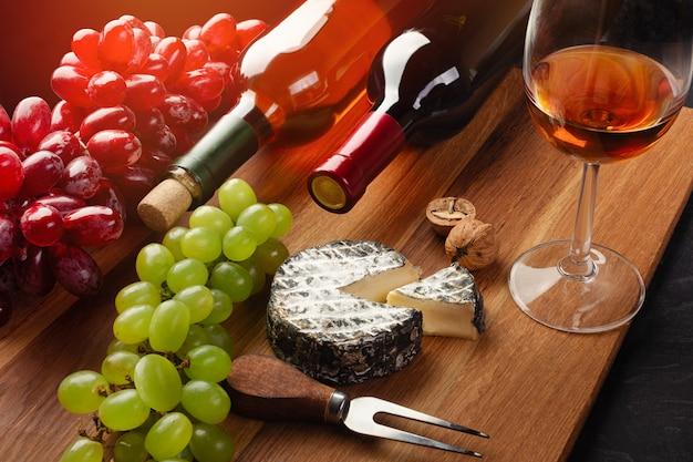 Garrafas de vinho vermelhas e brancas com cacho de uvas, cabeça de queijo, nozes e um copo de vinho na placa de madeira Foto Premium