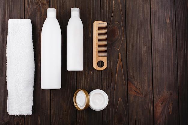 Garrafas de xampu e condicionador mentem com toalha e pente na mesa de madeira Foto gratuita