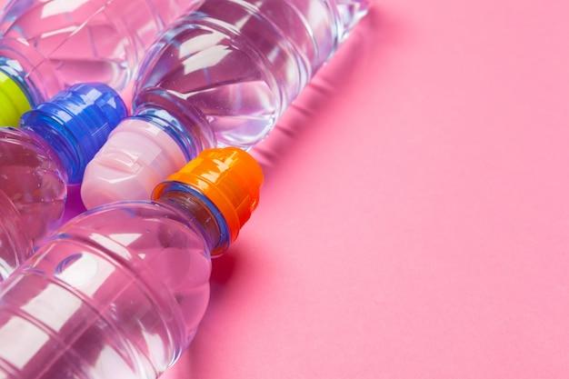 Garrafas plásticas com água pura no fundo rosa, copyspace Foto Premium