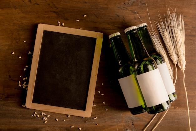 Garrafas verdes com etiqueta branca e quadro negro na mesa de madeira Foto gratuita