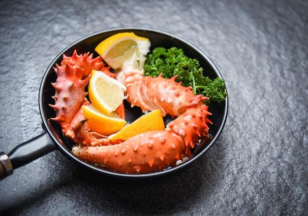 Garras de caranguejo cozido cozido marisco pan com alaskan king crab com limão salsa ervas e especiarias no escuro Foto Premium