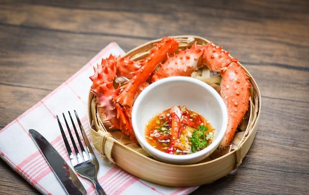 Garras de caranguejo cozidos cozidos em vapor de bambu com alaskan king crab e molho de frutos do mar na mesa de jantar Foto Premium