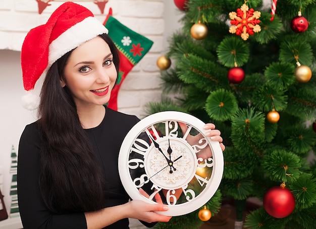 Gata do chapéu de papai noel com árvore de natal decorada e relógio velho Foto Premium