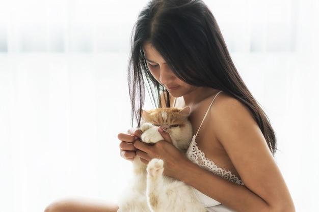 Gato de abraço garota sexy no quarto Foto Premium