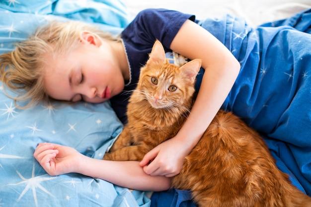 Gato fofo de gengibre com pequena menina dormindo na cama azul Foto Premium