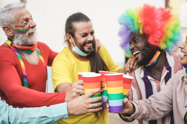 Gays multirraciais torcendo com óculos de arco-íris na parada do orgulho ao ar livre durante o surto de coronavírus - foco nos óculos Foto Premium