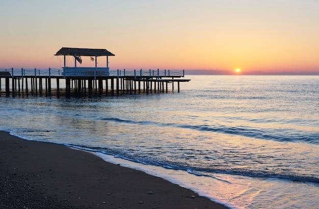 Gazebo no cais de madeira para o mar com o sol ao pôr do sol. Foto gratuita