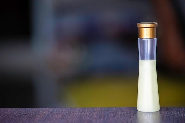 Gel de chuveiro pequeno da garrafa em uma tabela de madeira o fundo obscuro. Foto Premium