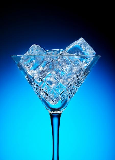 Gelo em um copo de martini em um fundo azul com um gradiente Foto Premium