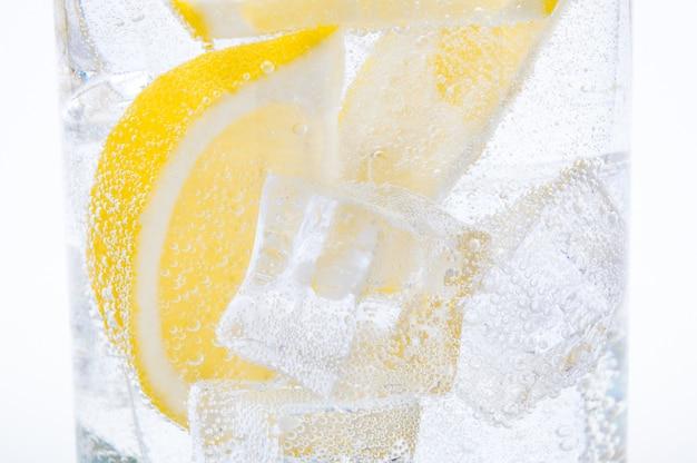 Gelo, fatias de limão e água limpa em um copo. Foto Premium