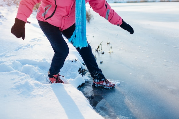 Gelo fino e perigoso. mulher corre o risco de pisar na superfície do rio congelado no inverno. cuidado, água insegura, possibilidade de queda Foto Premium