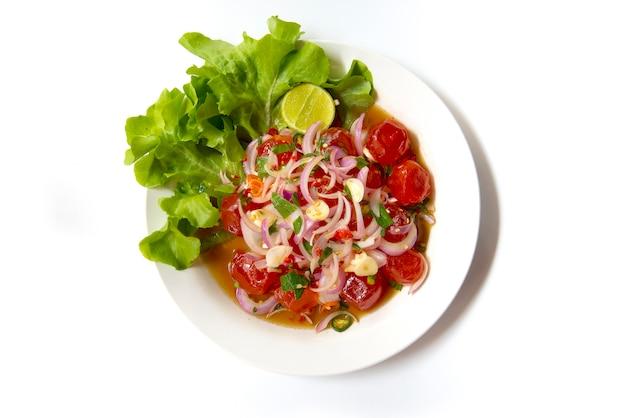 Gema salgada pasta picante do pimentão da salada. comida tailandesa no prato isolado no fundo branco Foto Premium