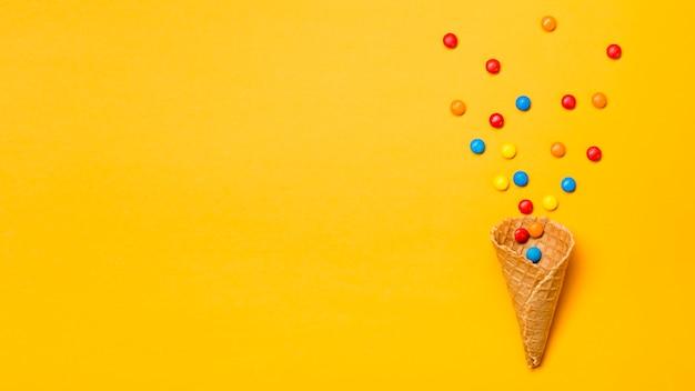 Gemas coloridas derramadas de cone de waffle em pano de fundo amarelo Foto gratuita
