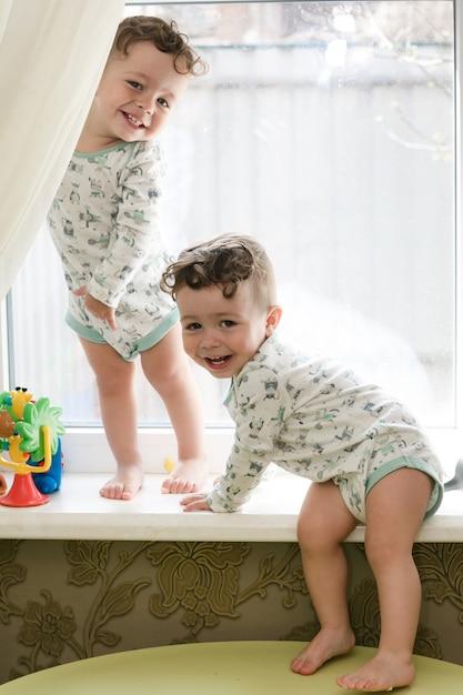 Gêmeos alegres - irmãos ficar em um peitoril da janela Foto Premium