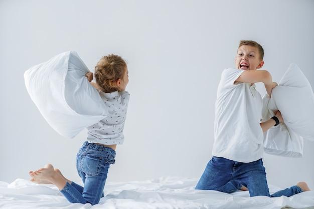Gêmeos impertinentes luta amigável com travesseiros na cama Foto Premium