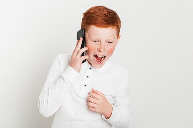 Gengibre, menino, gritando, enquanto, falando, ligado, smartphone Foto gratuita
