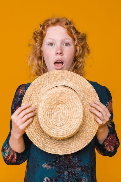 Gengibre surpreendeu jovem segurando o chapéu de palha Foto gratuita