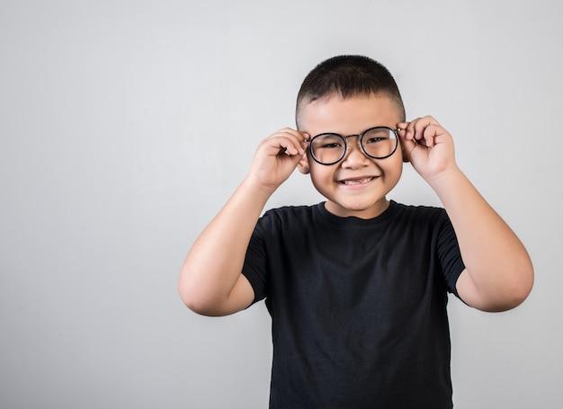 Gênio de menino engraçado usando óculos em estúdio tiro Foto gratuita