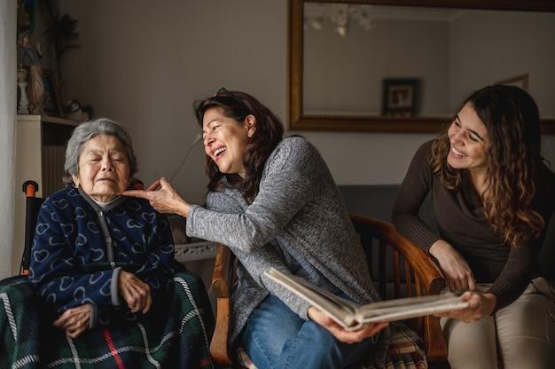 Geração de mulheres com a velha avó doente sentada na cadeira de rodas e sorrindo, filha e neta, olhando um álbum de fotos. Foto Premium