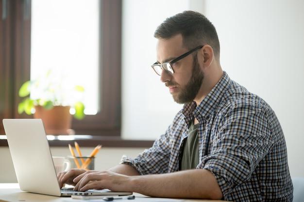 Geração milenar homem trabalhando no computador portátil para resolver o problema Foto gratuita