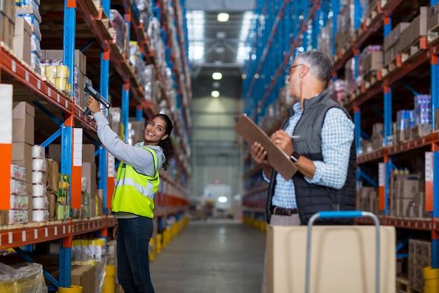 Gerente de armazém e trabalhadora interagindo enquanto trabalhava Foto Premium
