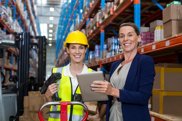 Gerente de armazém e trabalhadora sorrindo enquanto segura o tablet digital Foto Premium