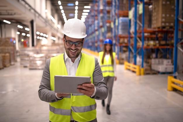 Gerente de armazém lendo relatório em tablet sobre entrega e distribuição bem-sucedidas no centro de logística do armazém Foto gratuita