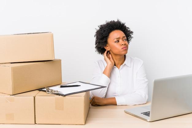 Gerente de armazém sentado verificando as entregas com laptop tocando atrás da cabeça, pensando e fazendo uma escolha. Foto Premium