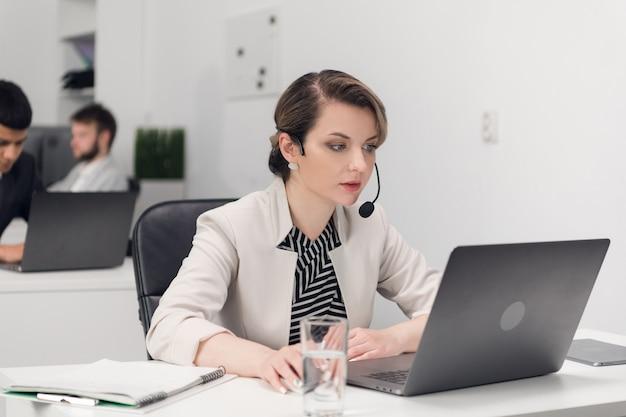 Gerente de atendimento ao cliente no local de trabalho à mesa com um laptop. Foto Premium