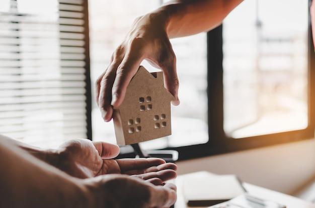 Gerente de corretor de imóveis dando modelo de casa para o cliente Foto Premium