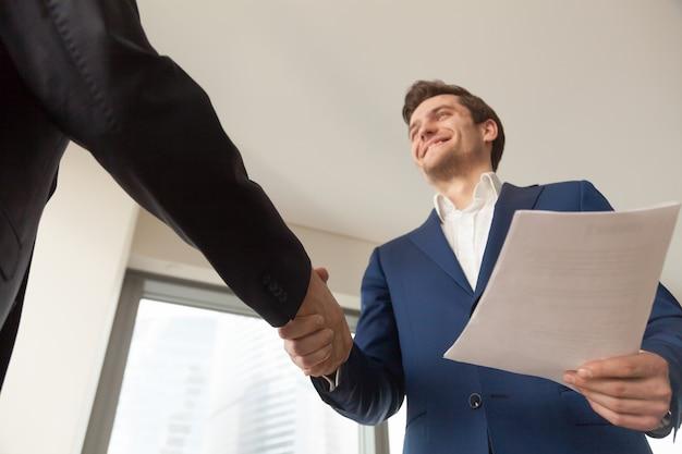 Gerente de empresa sorridente, congratulando-se com o cliente no escritório Foto gratuita