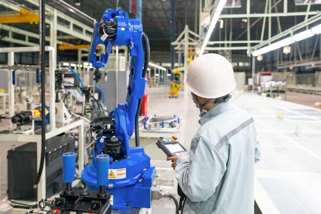 Gerente de engenheiro de verificação e controle de automação robô braços máquina na fábrica inteligente industrial Foto Premium