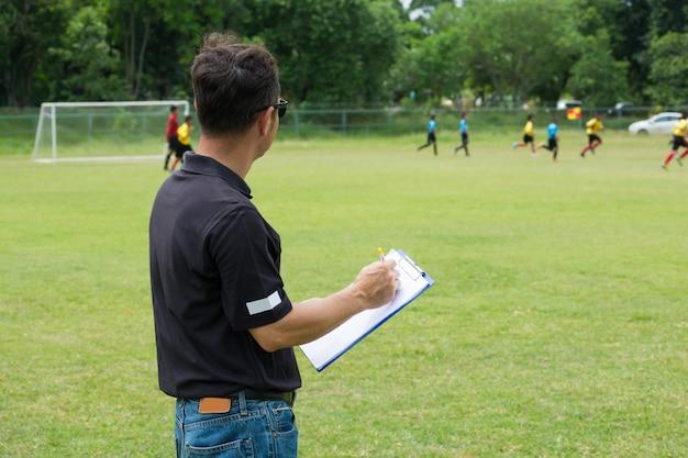 Gerente de equipe treinando sua tripulação ao lado do campo de futebol ou futebol Foto Premium