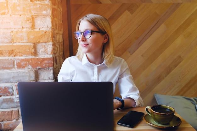 Gerente de garota, freelancer, senhora de negócios trabalhando em um laptop em um café ou co-working. Foto Premium