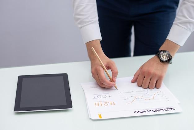 Gerente de marketing novo escrevendo notas no relatório no escritório Foto gratuita