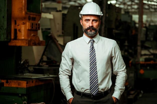 Gerente de projeto sênior trabalhando em fábrica industrial Foto Premium