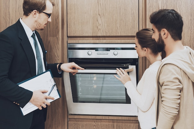 Gerente de terno está mostrando forno embutido para acoplar clientes Foto Premium