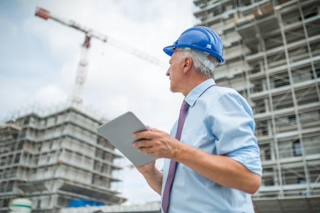 Gerente do site usando seu tablet na frente de um canteiro de obras Foto Premium