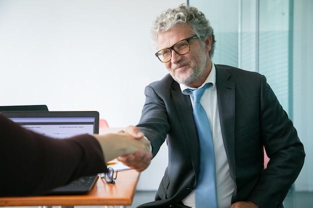 Gerente executivo barbudo caucasiano apertando a mão e sorrindo Foto gratuita